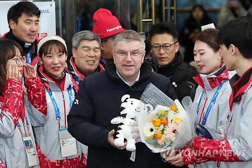 Tomas Bach (centro), recibe regalos de bienvenida por parte de voluntarios de los Juegos Olímpicos de Invierno de PyeongChang 2018, el 30 de enero de 2018, en la estación de Jinbu, en PyeongChang, en la provincia de Gangwon.
