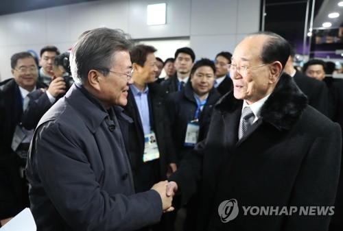 """El presidente de Corea del Sur, Moon Jae-in (izda.), sonríe mientras estrecha la mano del jefe de Estado ceremonial de Corea del Norte, Kim Yong-nam, el 10 de febrero de 2018, en el Centro de Hockey de Kwandong, en Gangneung, donde se disputó el partido de """"hockey"""" sobre hielo femenino entre el equipo intercoreano y el equipo suizo. (Foto proporcionada por la oficina presidencial, Cheong Wa Dae)"""