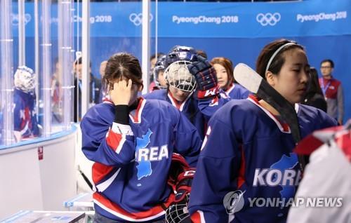"""El 12 de febrero del 2018, el equipo femenino de """"hockey"""" sobre hielo integrado por las dos Coreas sale de la pista con los hombros caídos tras perder contra Suecia, en el Centro de Hockey de Kwandong, en la ciudad de Gangneung, provincia de Gangwon."""