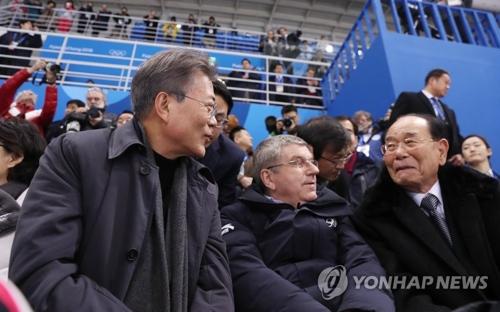"""El presidente surcoreano, Moon Jae-in (izda), Bach (centro) y el jefe de Estado ceremonial norcoreano, Kim Yong-nam, asisten al primer juego clasificatorio del equipo unificado femenino de """"hockey"""" sobre hielo entre las dos Coreas, realizado, el 10 de febrero de 2018, en Gangneung, Corea del Sur."""