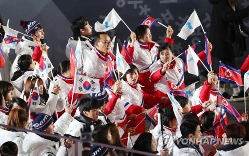 Los atletas surcoreanos y norcoreanos mueven sus propias banderas nacionales, marchando juntos durante la ceremonia de clausura de los Juegos Olímpicos de Invierno de PyeongChang, celebrada, el 25 de febrero de 2018, en el Estadio Olímpico de PyeongChang, al este de Seúl.