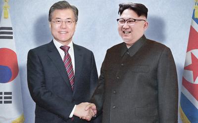 Este montaje fotográfico muestra al líder surcoreano, Moon Jae-in (izda.) estrechando la mano del líder norcoreano, Kim Jong-un.