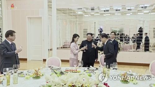 Esta imagen, tomada de las imágenes de la televisión estatal de Corea del Norte el 6 de marzo de 2018, muestra a Kim Jong-un (centro) y a su esposa, Ri Sol-ju, brindando con Chung Eui-yong, el jefe de la delegación de enviados especiales de Corea del Sur, un día antes.