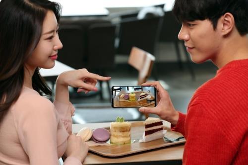 En la imagen, desvelada, el 8 de marzo del 2018, por LG Electronics Inc., los modelos posan con el teléfono inteligente V30S ThinQ de la firma.
