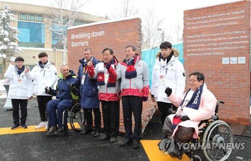 El presidente del Comité Paralímpico Internacional, Andrew Parsons (4º por la izda.); el jefe del Comité Organizador de PyeongChang para los Juegos Olímpicos y las Paralimpiadas de Invierno de 2018 (POCOG), Lee Hee-beom (5º por la izda.), y el ministro de Deportes de Corea del Sur, Do Jong-hwan (3º por la dcha.), posan ante la cámara, el 8 de marzo de 2018, durante una ceremonia de las Paralimpiadas en la Villa Olímpica de PyeongChang, provincia de Gangwon.