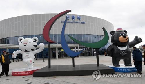 El emblema de los Juegos Paralímpicos de PyeongChang se exhibe, el 6 de marzo de 2018, entre la mascota de las paralimpiadas, Bandabi (dcha.) y la mascota de las olimpiadas, Soohorang, en la estación de Gangneung, provincia de Gangwon.