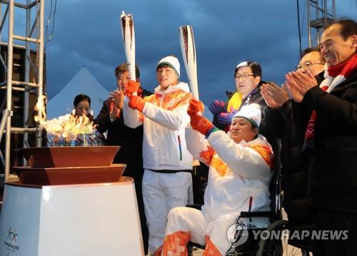 """El piloto surcoreano de """"skeleton"""", Yun Sung-bin (2º por la izda.), sostiene la antorcha durante el relevo de los Juegos Paralímpicos de PyeongChang, el 5 de marzo de 2018, en Chuncheon, provincia de Gangwon."""