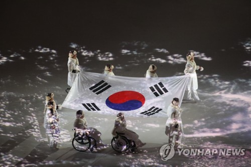 """La bandera nacional surcoreana, o """"Taegukgi"""", se lleva dentro del Estadio Olímpico de PyeongChang, provincia de Gangwon, durante la ceremonia de inauguración de los Juegos Paralímpicos de Invierno de PyeongChang, el 9 de marzo de 2018."""