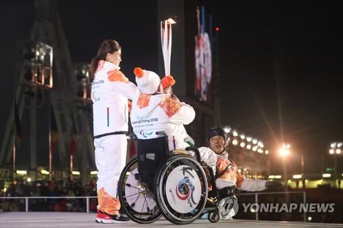 """Kim Eun-jung, jugadora del equipo de """"curling"""" femenino de Corea del Sur en los Juegos Olímpicos de Invierno de PyeongChang, y Seo Soon-seok, miembro del equipo de curling en silla de ruedas en los Juegos Paralímpicos de Invierno de PyeongChang encienden el pebetero paralímpico."""