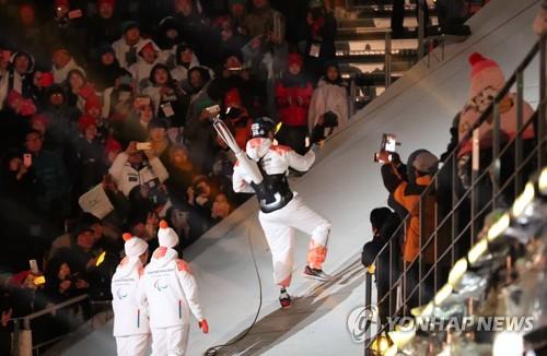"""El capitán de """"hockey"""" sobre hielo paralímpico de Corea del Sur, Han Min-su, llevaba la antorcha en la espalda y con una cuerda subió por la pendiente en la ceremonia de apertura de los Juegos Paralímpicos de Invierno de PyeongChang, el 9 de marzo de 2018."""