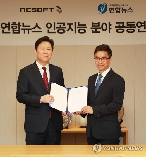 Lee Ki-chang (izda.), director ejecutivo de estrategia de gestión de la Agencia de Noticias Yonhap, y Lee Jae-joon, jefe de la división exclusiva a cargo de la investigación de la IA de NCSOFT, posan para una fotografía, el 16 de mayo de 2018, en la sede de Yonhap, después de firmar un acuerdo sobre la cooperación en la IA .