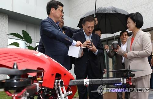 El presidente Moon Jae-in (2º por la izda.) toma un sorbo de café entregado por un pequeño vehículo aéreo no tripulado controlado a remoto mientras asiste a una reunión especial para verificar el progreso de su estrategia de crecimiento liderada por la innovación, en Seúl, el 17 de mayo de 2018.