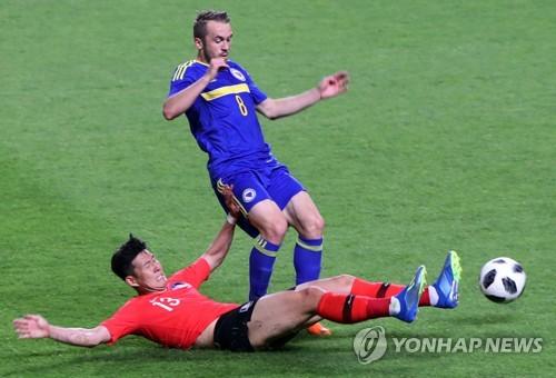 Son Heung-min (de rojo), de Corea del Sur, hace una entrada a Edin Visca, de Bosnia y Herzegovina, en un partido de preparación para la Copa del Mundo en el World Cup Stadium de Jeonju, a 240 kilómetros al sur de Seúl, el 1 de junio de 2018.