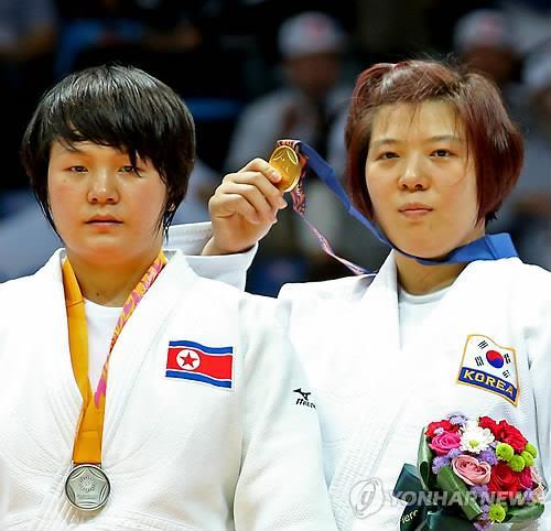 En la imagen de archivo, tomada el 22 de septiembre de 2014, la judoka surcoreana Jeong Gyeong-mi (dcha.), muestra su medalla de oro tras vencer a su oponente norcoreana, Sol Kyong, en la categoría femenina de menos de 78 kilogramos en los Juegos Asiáticos de Incheon.
