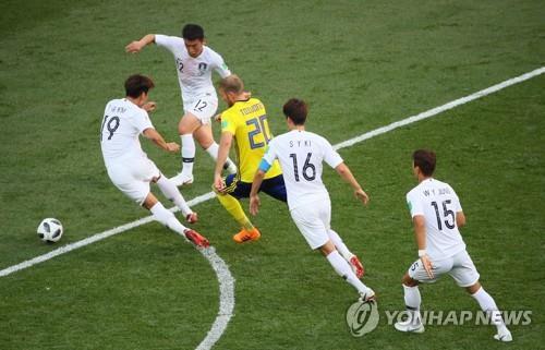 Los jugadores surcoreanos (de blanco) intentan defender a Andreas Granqvist, de Suecia, en su partido disputado el 18 de junio de 2018, en Rusia, durante la Copa Mundial.