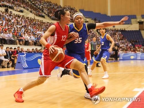 La norcoreana Ro Suk-yong (izda.) intenta pasar a Kim Han-byul, de Corea del Sur, durante un partido amistoso de baloncesto en el gimnasio Ryugyong Chung Ju-yung de Pyongyang, el 5 de julio de 2018. (Foto del cuerpo de prensa)