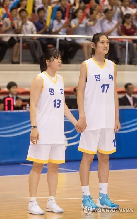 """La surcoreana Kim So-dam (izda.) y la norcoreana Pak Jin-a se cogen de la mano durante un partido de baloncesto femenino intercoreano entre las jugadores del """"Equipo de la paz"""" y del """"Equipo de la prosperidad"""" en el gimnasio Ryugyong Chung Ju-yung de Pyongyang, el 4 de julio de 2018. Las jugadoras de las dos Coreas se combinaron en los dos equipos. (Foto del cuerpo de prensa)"""