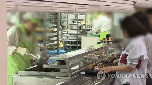Las personas esperan su turno para recibir su ración de comida en el comedor de una empresa surcoreana.