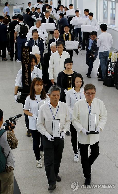 El 18 de septiembre de 2015, las familias de las víctimas y miembros de grupos civiles llevan las lápidas mortuorias y urnas que contienen los restos de 115 coreanos obligados por Japón a realizar trabajos forzosos durante el régimen colonial japonés de 1910-45, después de llegar a una terminal internacional de ferris en la ciudad portuaria de Busan, en el sur de Corea del Sur. Los restos han sido reunidos desde 1997, en todo Hokkaido, por expertos, religiosos y estudiantes de ambos países. (Foto de archivo)
