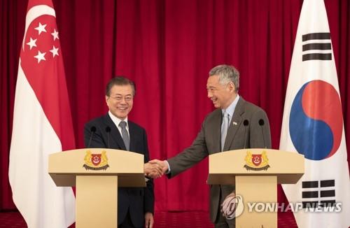 El presidente de Corea del Sur, Moon Jae-in (izda.), y el primer ministro de Singapur, Lee Hsien Loong, se dan la mano después de una conferencia de prensa conjunta para anunciar el resultado de su cumbre bilateral, celebrada en Singapur el 12 de julio de 2018.