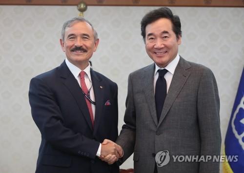 El primer ministro Lee Nak-yon, estrecha la mano del embajador de los Estados Unidos ante Seúl Harry Harris durante una reunión celebrada el 8 de agosto de 2018 en Seúl