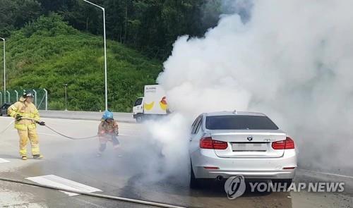 La imagen, proporcionada por el Servicio Contraincendios de la provincia de Gyeonggi, muestra un coche BMW envuelto en humo causado por un incendio en el compartimento del motor del coche mientras iba circulando, el 9 de agosto del 2018, por una carretera cerca de Anyang, provincia de Gyeonggi.