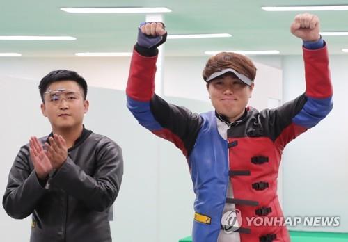 El tirador surcoreano Jeong You-jin (dcha.) celebra la medalla de oro en el evento masculino de blanco móvil de 10 metros en la 18ª edición de los Juegos Asiáticos en el Campo de Tiro de la Ciudad Deportiva de Jakabaring, en Palembang, Indonesia, el 24 de agosto de 2018. A la izquierda está Pak Myong-won, de Corea del Norte, que se llevó la plata.