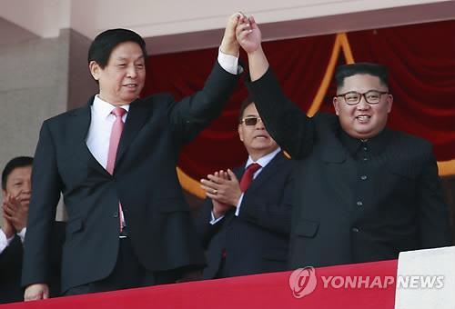 El presidente del Comité de Asuntos de Estado de Corea del Norte, Kim Jong-un (dcha.), levanta la mano junto con Li Zhanshu, miembro del Comité Permanente del Politburó del Partido Comunista de China, en una grada durante un desfile militar en marcha en el centro de Pyongyang, el 9 de septiembre de 2018, para celebrar el 70º aniversario de su fundación. (EPA-Yonhap)