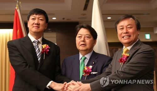 En la imagen, tomada el 13 de septiembre de 2018, se muestra, de izquierda a derecha, al director adjunto de la Administración General del Deportes de China, Gao Zhidan; al ministro de Deportes japonés, Yoshimasa Hayashi, y a su homólogo surcoreano, Do Jong-whan, en Tokio, dándose la mano después de una reunión trilateral.