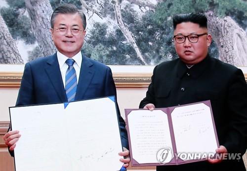 El 19 de septiembre de 2018, el presidente surcoreano, Moon Jae-in (izda.), y el presidente del Comité de Asuntos de Estado norcoreano, Kim Jong-un, posan después de firmar un acuerdo de su tercera reunión cumbre en Pyongyang, en esta imagen emitida en vivo desde el centro de prensa en Seúl.