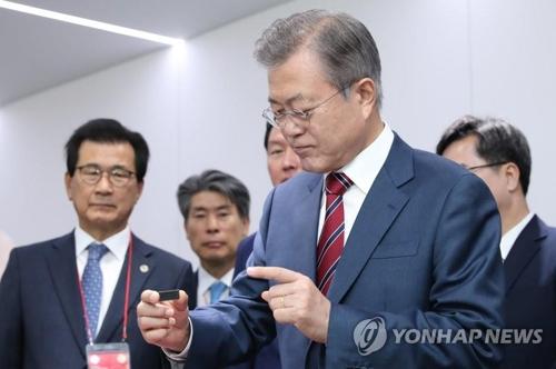 El 4 de octubre del 2018, el presidente surcoreano, Moon Jae-in, observa una memoria chip en la fábrica de SK hynix durante su visita para asistir a la ceremonia en conmemoración de la construcción de nuevas líneas de ensamblaje de la firma.