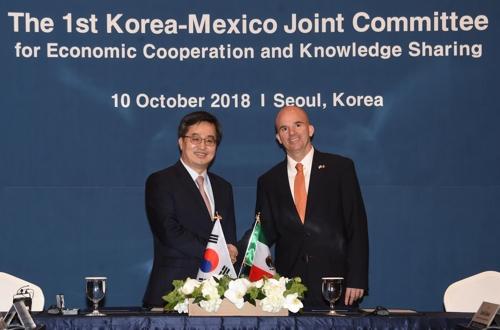 El vice primer ministro surcoreano, Kim Dong-yeon (izda.), y su homólogo mexicano, José Antonio González Anaya, posan ante la cámara, el 10 de octubre de 2018, en un hotel de Seúl.
