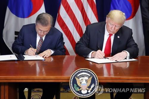 El presidente de Corea del Sur, Moon Jae-in (izda.), y el presidente de Estados Unidos, Donald Trump, firman el documento oficial sobre el tratado de libre comercio (TLC) revisado entre los dos aliados en el Lotte New York Palace, en Nueva York, el 24 de septiembre de 2018. (Foto de archivo)