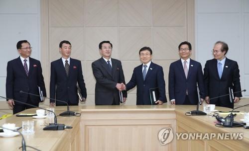 El viceministro de Salud y Bienestar Social surcoreano, Kwon Deok-cheol (tercero por la dcha.), y su homólogo norcoreano, Park Myong-su (tercero por la izda.), se estrechan la mano antes de sostener diálogos sanitarios, el 7 de noviembre de 2018, en la oficina de enlace intercoreana de Kaesong, Corea del Norte.