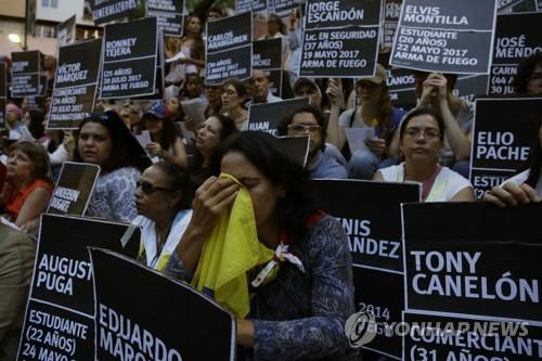 시위 희생자들의 이름이 적힌 피켓을 든 베네수엘라 반정부 시위대