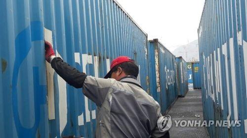 컨테이너에 붙은 한진해운 로고 제거[연합뉴스 자료사진]