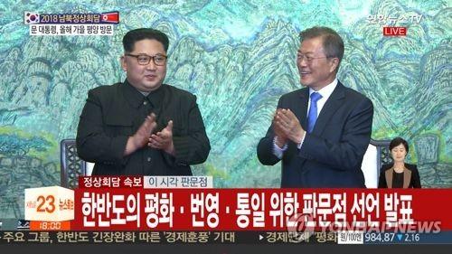 韩朝领导人在签署《板门店宣言》后鼓掌。(韩联社TV提供)