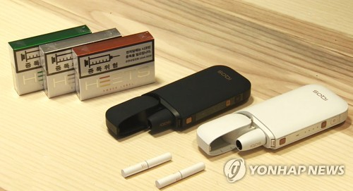 This file photo shows tobacco the heating device IQOS and tobacco sticks Heets. (Yonhap)