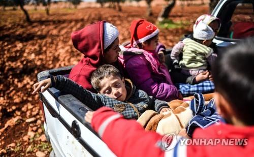 트럭 짐칸에 타고 피란 가는 시리아 쿠르드 아이들