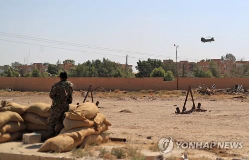 시리아 동부 샤다디에서 미군 치누크 헬기를 지켜 보는 시리아민주군 대원
