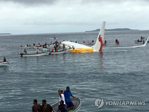 미크로네시아에서 비행기가 불시착하자 소형 어선들이 승객들을 구조하고 있다.
