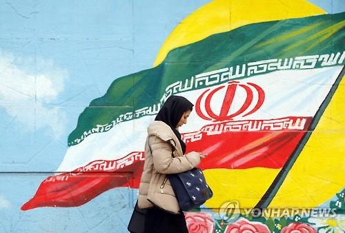 이란 국기가 그려진 테헤란 거리를 걸어가는 여성 [EPA=연합뉴스]