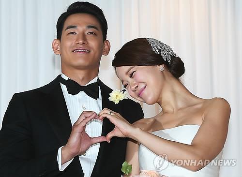 资料图片:2013年6月2日,郑锡元(左)与白智英举行婚礼,图为两人在婚礼开始前摆姿势供媒体拍照。(韩联社)