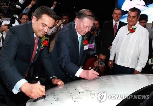 昨年9月、起亜のメキシコ工場完工式で関係者と「K3」にサインする鄭夢九(チョン・モング)現代自動車グループ会長(左から2人目、現代・起亜提供)=(聯合ニュース)
