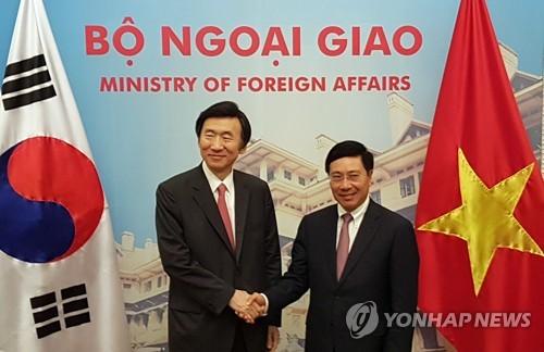 3月20日,在越南首都河内,尹炳世(左)与范平明在会谈前握手合影。(韩联社)