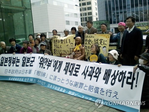 23日、日本総領事館前の少女像の元を訪れた日本平和委員会のメンバー=24日、釜山(聯合ニュース)