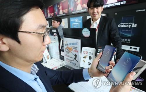 Les précommandes pour le nouveau smartphone de Samsung Electronics, Galaxy S8, s&apos;ouvrent ce vendredi 7 avril 2017 et un client regarde le smartphone phare de Samsung dans une boutique de téléphones mobiles à Séoul.</p><p>(Yonhap)