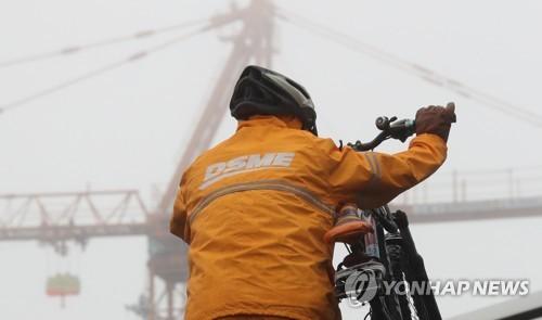 资料图片:2017年4月17日,在庆尚南道巨济市,一名大宇造船海洋公司玉浦造船厂的员工在上班途中。(韩联社)