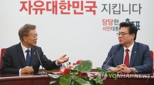 5月10日上午,在自由韩国党办公楼,文在寅(左)会见自由韩国党国会代表郑宇泽。(韩联社)