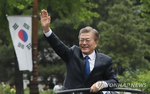 Le président Moon Jae-in  salue de la main des citoyens lors d'un défilé en voiture sur le chemin du palais présidentiel Cheong Wa Dae, le mercredi 10 mai 2017, après avoir prêté serment à l'Assemblée nationale.